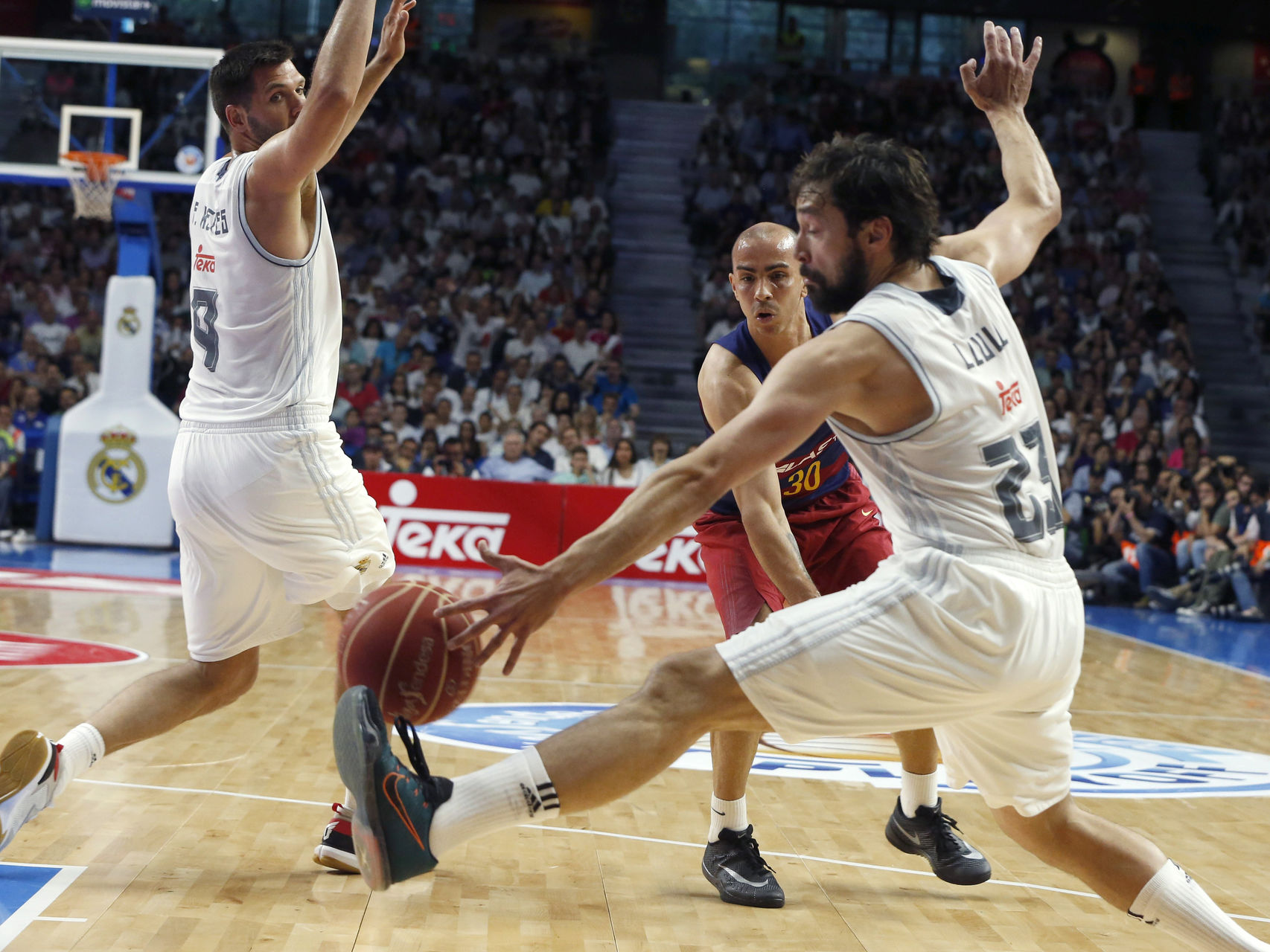 Reyes y Llull intentan impedir un pase de Arroyo.